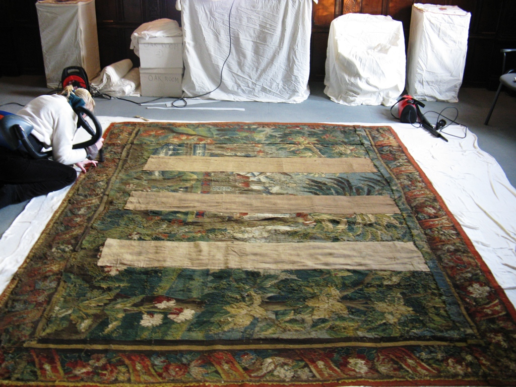 Surface cleaning a tapestry on site.