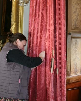 The curtain shown above, now loose, with conservator hard at work on it.