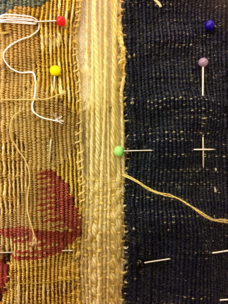During conservation, inserting new warps along the lower edge and stitching them down