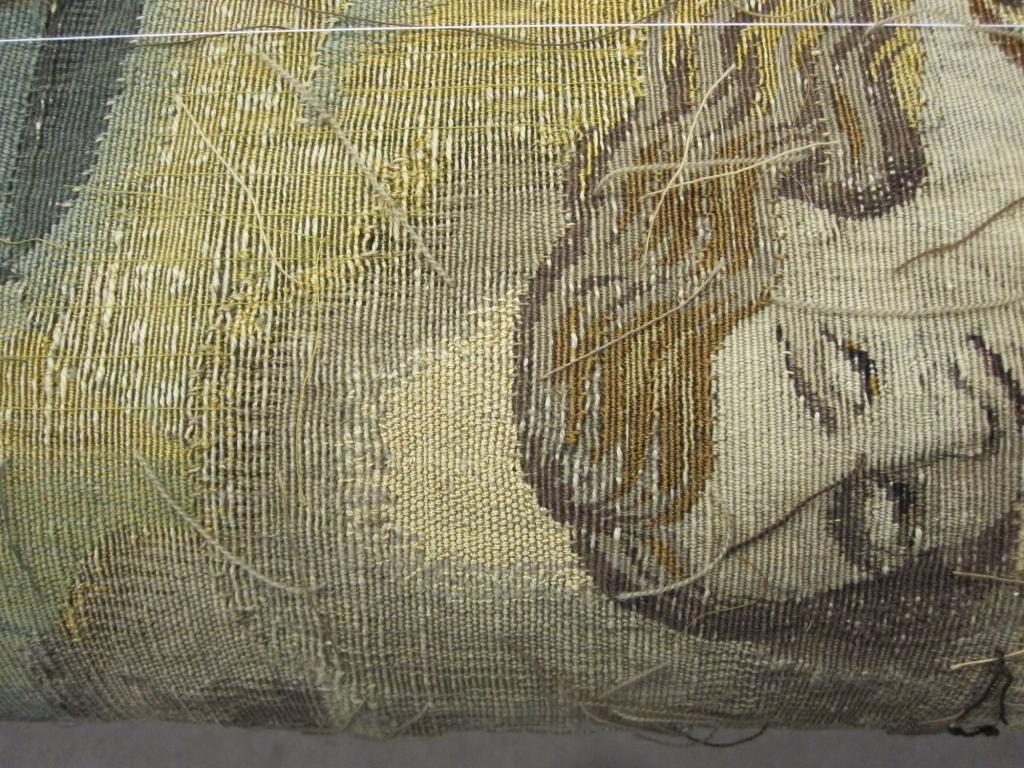 A previous woven repair was left in place above the figure's head, and the area around it strengthened